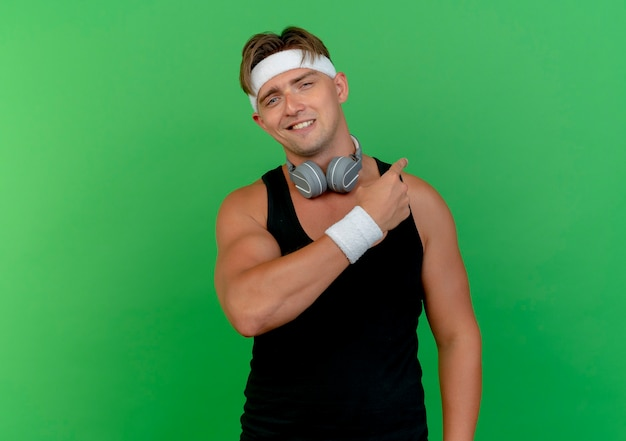 Jovem bonito e esportivo sorridente usando bandana e pulseiras com fones de ouvido apontando para trás, isolado na parede verde