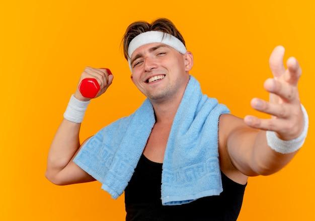 Jovem bonito e esportivo sorridente usando bandana e pulseiras com uma toalha em volta do pescoço, segurando um haltere esticando a mão na frente, isolado na parede laranja