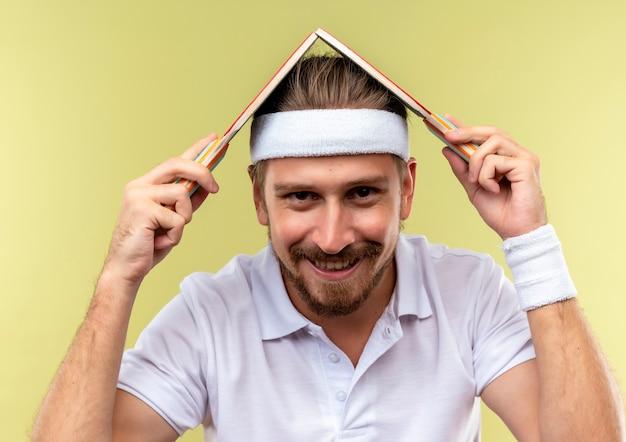Jovem bonito e esportivo sorridente, usando bandana e pulseiras segurando raquetes de pingue-pongue na cabeça, parecendo isolado em um espaço verde
