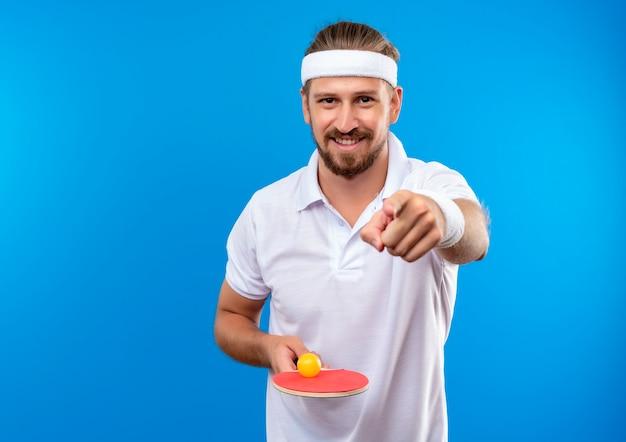 Jovem bonito e esportivo sorridente, usando bandana e pulseiras, segurando uma raquete de pingue-pongue com uma bola e apontando isolado no espaço azul