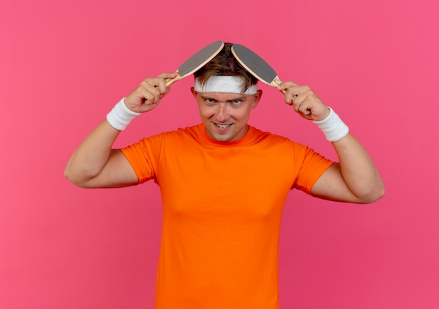 Jovem bonito e esportivo sorridente usando bandana e pulseiras tocando a cabeça com raquetes de pingue-pongue isoladas na parede rosa