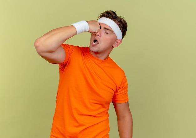 Jovem bonito e esportivo usando bandana e pulseiras, chutando-se em um olho isolado em fundo verde oliva com espaço de cópia