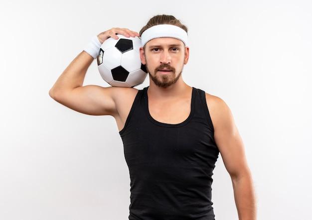 Jovem bonito e esportivo usando bandana e pulseiras segurando uma bola de futebol no ombro, parecendo isolado no espaço em branco