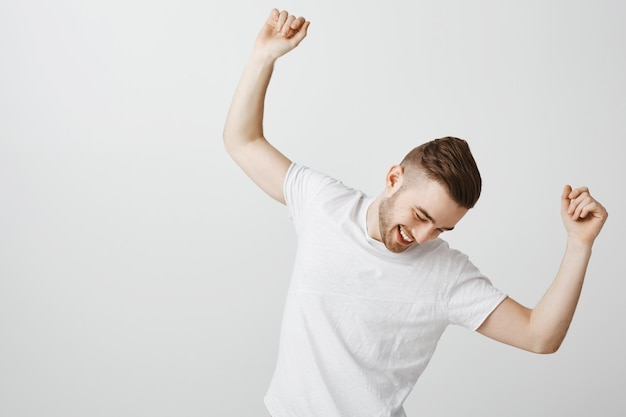 Jovem bonito e feliz dançando com uma camiseta branca sobre uma parede cinza