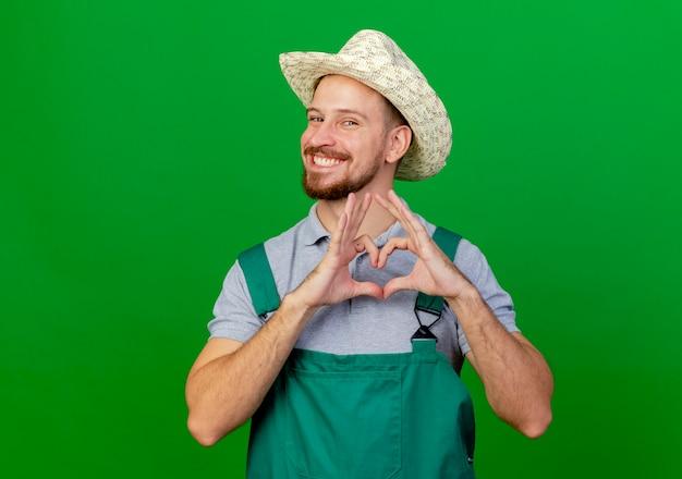 Jovem bonito e feliz jardineiro eslavo de uniforme e chapéu olhando fazendo sinal de coração