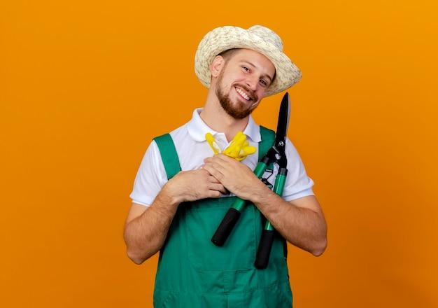 Jovem bonito e feliz jardineiro eslavo de uniforme, usando um chapéu, segurando luvas de jardinagem e podadores parecendo isolados