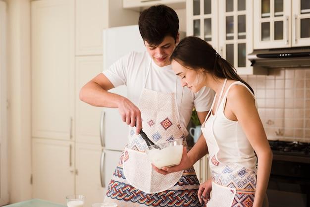 Jovem bonito e mulher juntos a preparar bolos