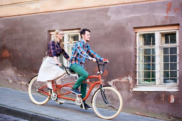 Jovem bonito e mulher loira e bonita, montando bicicleta dupla em tandem ao longo da calçada pavimentada no dia ensolarado ensolarado de outono por edifícios antigos com paredes rachadas e treliça de ferro nas janelas.