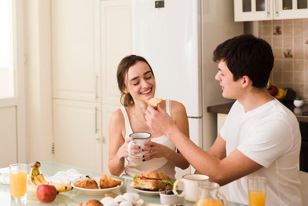 Jovem bonito e mulher tomando café da manhã