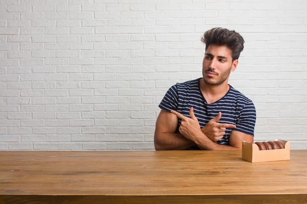 Jovem bonito e natural homem sentado em uma mesa confuso e duvidoso, decidir entre tw