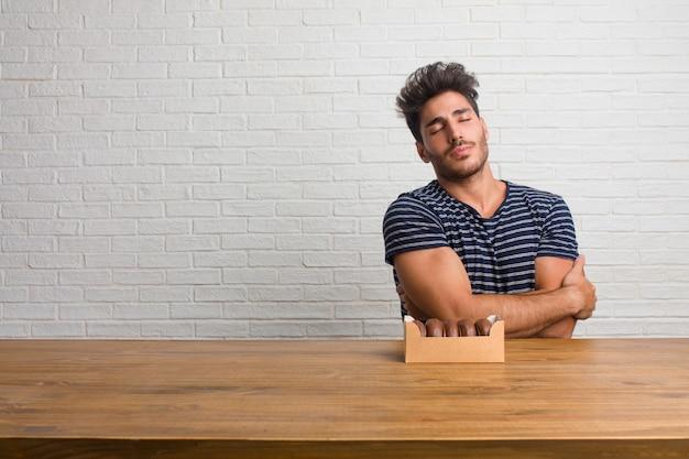 Jovem bonito e natural homem sentado em uma mesa orgulhosa e confiante, apontando os dedos