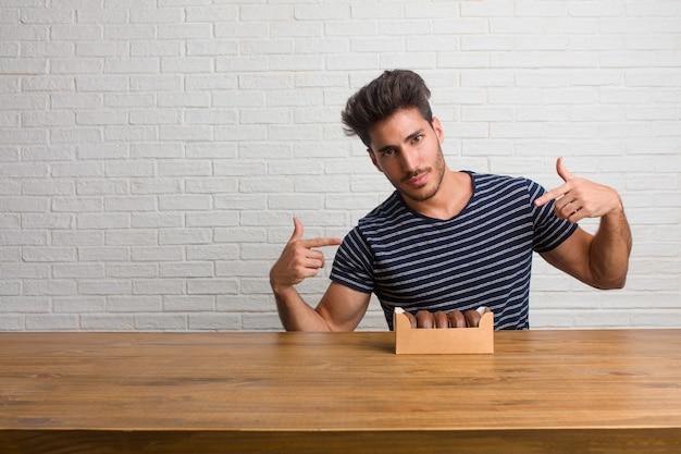 Jovem bonito e natural, sentado em uma mesa orgulhosa e confiante, apontando os dedos, exemplo a seguir