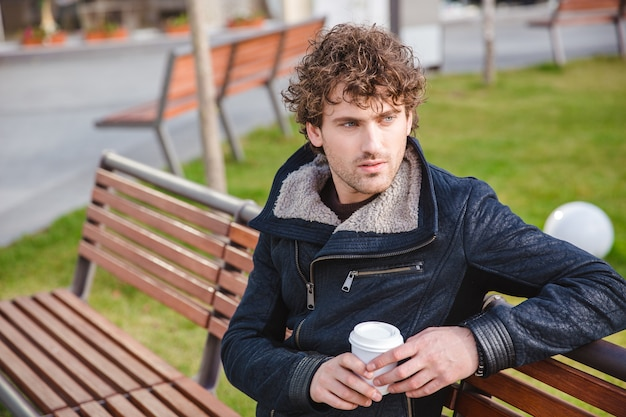 Jovem bonito e pensativo, encaracolado, com uma jaqueta preta, sentado em um banco de madeira no parque e bebendo café