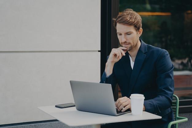 Jovem bonito e pensativo navegando na web em um laptop enquanto trabalhava remotamente em um café na calçada