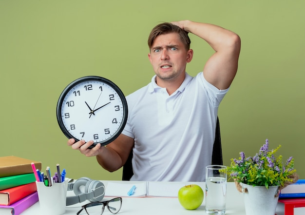 Jovem bonito e preocupado estudante do sexo masculino sentado na mesa com as ferramentas da escola, segurando o relógio de parede e colocando a mão na cabeça isolada no verde oliva