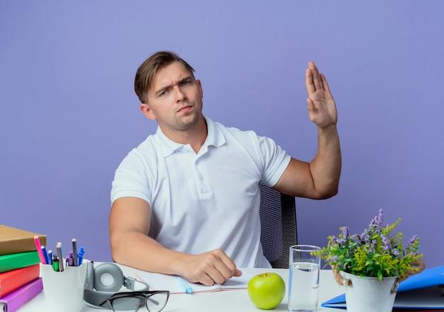 Jovem bonito e rigoroso estudante sentado à mesa com as ferramentas da escola estendidas de mãos dadas isoladas