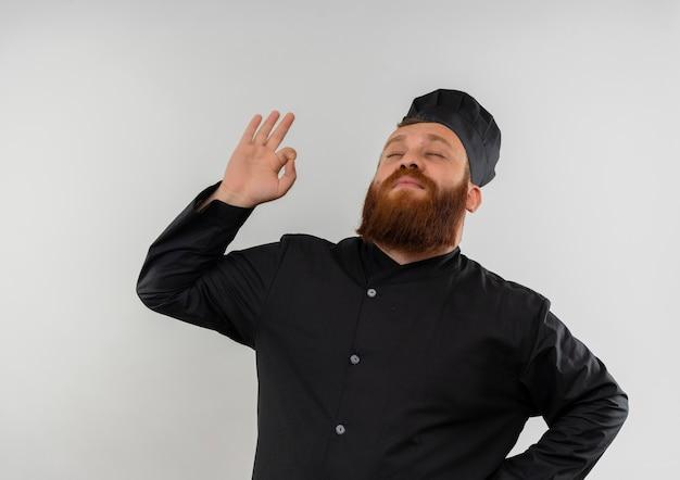 Jovem bonito e satisfeito com uniforme de chef, fazendo sinal de ok com os olhos fechados, isolado no espaço em branco
