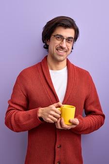 Jovem bonito e sorridente bebendo chá de manhã, aproveite a vida