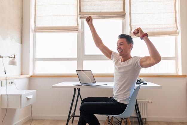 Jovem bonito e sorridente em roupa casual sentado à mesa trabalhando no laptop, freelancer em casa