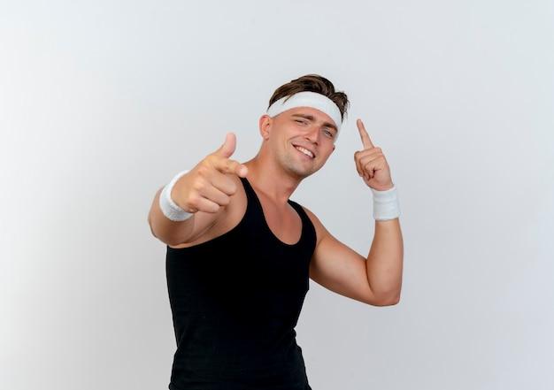 Jovem bonito e sorridente homem desportivo usando fita para a cabeça e pulseiras apontando para cima e para a frente, isoladas na parede branca