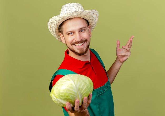 Jovem bonito e sorridente jardineiro eslavo de uniforme e chapéu estendendo o repolho e olhando para manter a outra mão no ar isolado