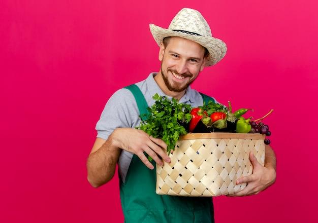 Jovem bonito e sorridente jardineiro eslavo de uniforme e chapéu segurando uma cesta de legumes olhando