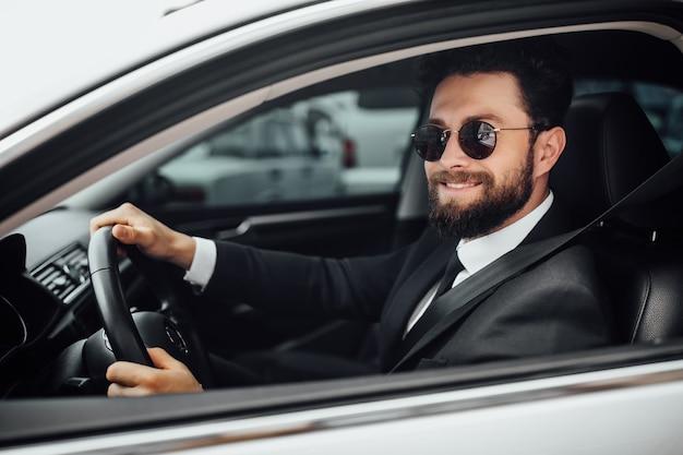 Jovem bonito e sorridente motorista barbudo vestindo terno completo com cinto de segurança preso, dirigindo um carro novo branco