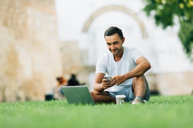 Jovem bonito e sorridente sentado na grama do parque com as pernas cruzadas, usando o telefone celular e o laptop prateado