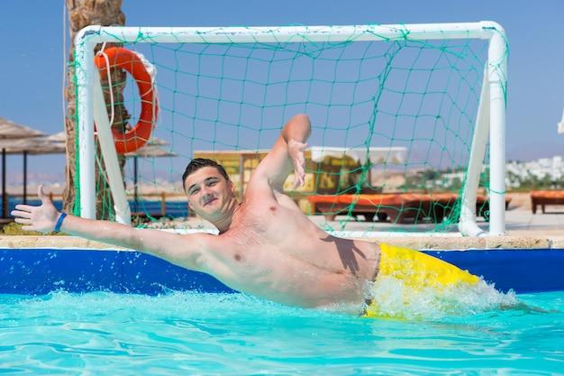 Jovem bonito em ação jogando pólo aquático no hotel em um dia ensolarado de verão
