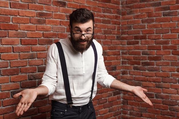 Jovem bonito em copos gesticulando na parede de tijolo.