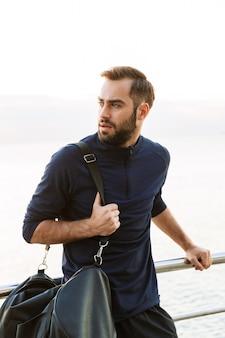 Jovem bonito em forma de esportista carregando uma bolsa em pé ao ar livre