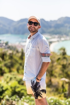 Jovem bonito em óculos de sol, apreciando a vista no ponto de vista da ilha de phi phi.