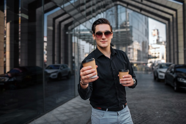 Jovem bonito em óculos de sol fica e detém dois copos com bebida. ele tem um mais perto de si. jovem parece.