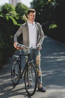Jovem bonito em pé com a bicicleta na rua