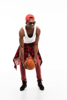 Jovem bonito em pé e brincando com bola de basquete