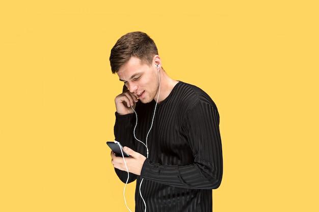 Jovem bonito em pé e ouvir música.