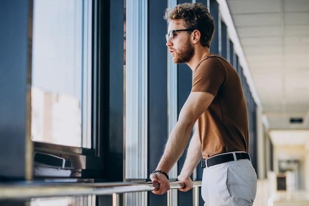 Jovem bonito em pé junto à janela no aeroporto