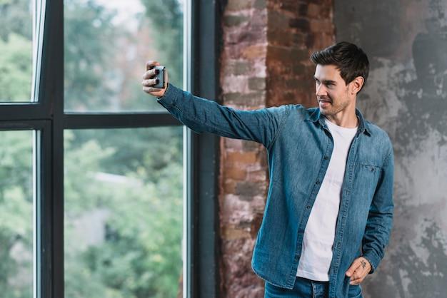 Jovem bonito em pé perto da janela, tendo selfie no telemóvel