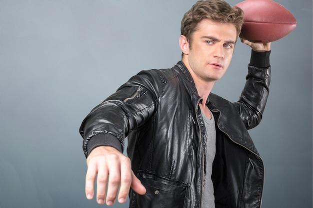Jovem bonito em roupas casuais está segurando uma bola de futebol americano