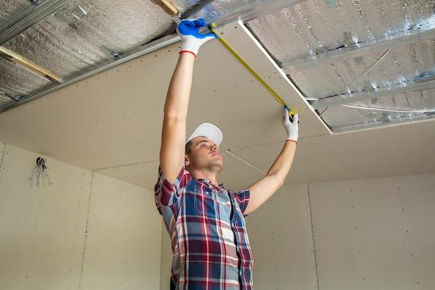 Jovem bonito em roupas casuais leva a medição do teto suspenso de drywall conectado à armação de metal.