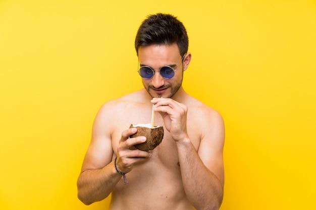 Jovem bonito em roupas de verão com um coquetel em um coco