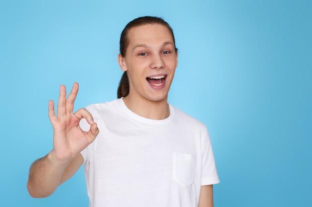 Jovem bonito em t-shirt mostrando o gesto de ok isolado sobre fundo azul. emoções humanas, expressões faciais