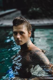 Jovem bonito em tatuagens descansando na piscina ao ar livre.