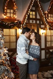 Jovem bonito em um suéter aconchegante e uma linda mulher em um vestido de tricô aconchegante olhando um para o outro ne ...