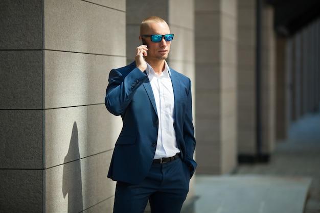 Jovem bonito em um terno de verão em uma caminhada em óculos de sol com um telefone na mão