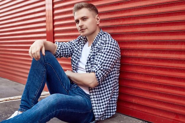 Jovem bonito em uma camisa e calça jeans perto do portão vermelho
