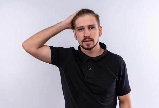 Jovem bonito em uma camisa pólo preta parecendo confuso tocando a cabeça em pé sobre um fundo branco