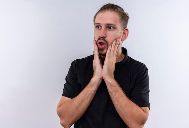 Jovem bonito em uma camisa pólo preta parecendo surpreso e surpreso tocando o rosto em pé sobre um fundo branco
