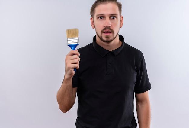 Jovem bonito em uma camisa pólo preta segurando um pincel e parecendo surpreso em pé sobre um fundo branco