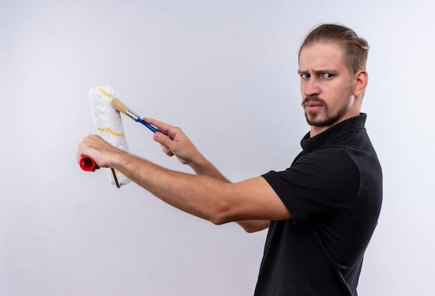 Jovem bonito em uma camisa pólo preta segurando um rolo de pintura e um pincel olhando de lado e carrancudo em pé sobre um fundo branco